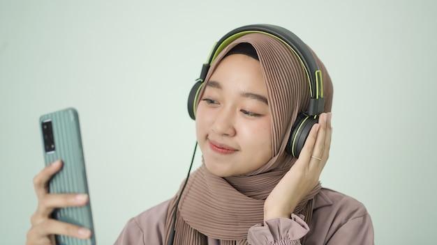 Piękna kobieta w hidżabie słucha z telefonu komórkowego szczęśliwie w domu