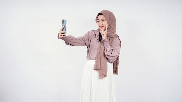 Piękna kobieta w hidżabie uśmiechający się wyraz wskazujący na ładny policzek na białym tle