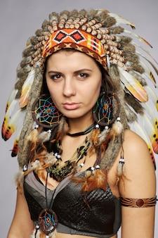 Piękna kobieta w indiańskich strojach z piórami