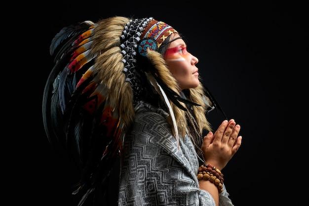 Piękna kobieta w indyjskim kapeluszu z piórami, dodatkami bohemians i boho, patrzy w górę, modli się. na białym tle czarna ściana