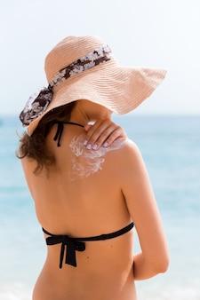 Piękna kobieta w kapeluszu kładzie krem przeciwsłoneczny na jej ramieniu na plaży.