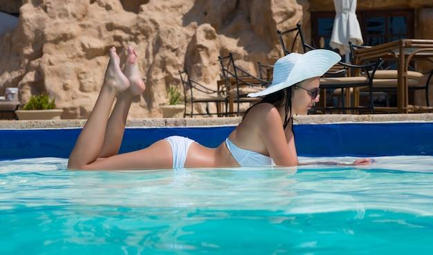 Piękna kobieta w kapeluszu leżąca na brzegu basenu w hotelu w słoneczny letni dzień