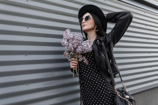 Piękna kobieta w kapeluszu moda w modnych okularach przeciwsłonecznych w czarne modne wiosenne ubrania ze skórzaną torbą z kwiatami bzu w ręce spoczywa w pobliżu metalowej ściany na zewnątrz w dzień wiosny. atrakcyjny model dziewczyny