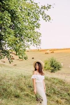 Piękna kobieta w kapeluszu na łące