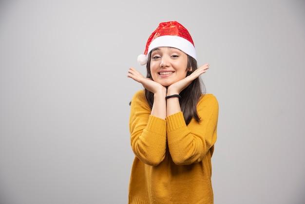 Piękna kobieta w kapeluszu santa czuje się szczęśliwa na szarej ścianie.