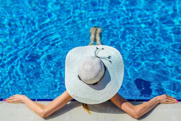 Piękna kobieta w kapeluszu siedząca na brzegu basenu