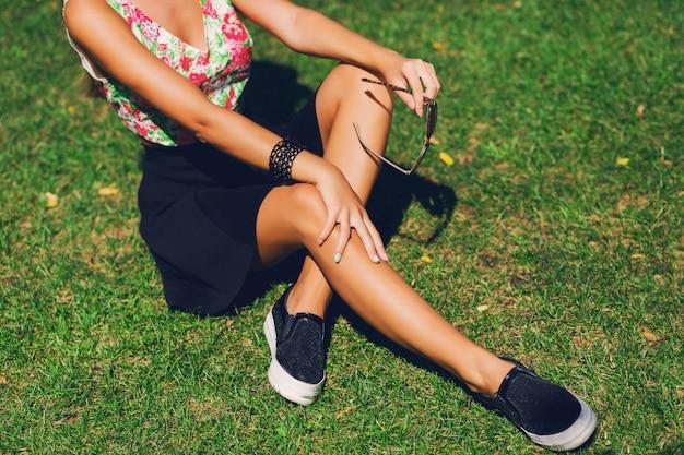 Piękna kobieta w kapeluszu siedzi na trawie