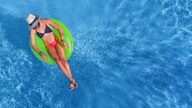 Piękna kobieta w kapeluszu w basenie widok z lotu ptaka z góry, młoda dziewczyna relaksuje się i bawi się na dmuchanym ringu