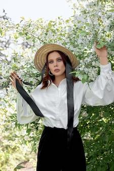 Piękna kobieta w kapeluszu wiosną w gałęziach kwitnących krzewów jabłoni