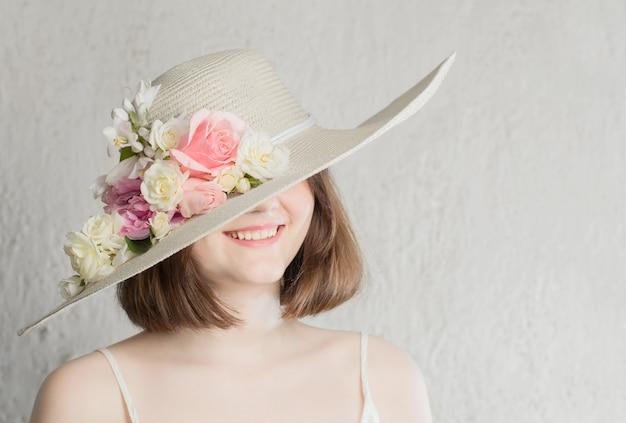 Piękna kobieta w kapeluszu z kwiatami