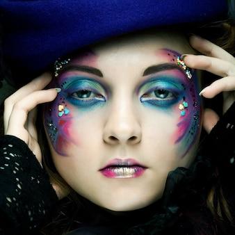 Piękna kobieta w kapeluszu z makijażem artystycznym.