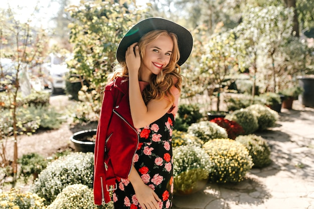 Piękna kobieta w kapeluszu z szerokim rondem zalotnie dotyka włosów. kobieta w czerwonej kurtce i sukni z różami uśmiecha się w ogrodzie.