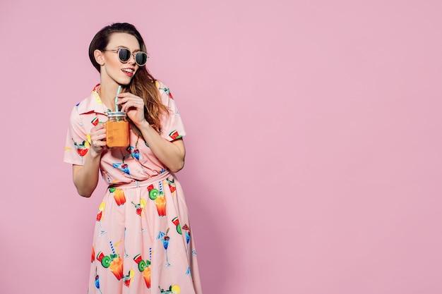 Piękna kobieta w kolorowej sukience z drukowanymi owocami pozowanie ze szklanką soku