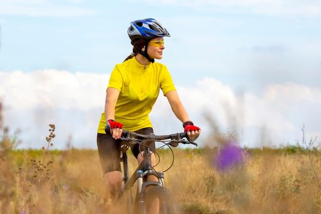 Piękna kobieta w kolorze żółtym, jazda na rowerze w przyrodzie. sport i rekreacja. hobby i zdrowie.