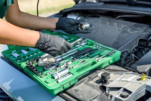 Piękna kobieta w kombinezonie z kluczami, naprawiająca zepsuty samochód w jej podróży