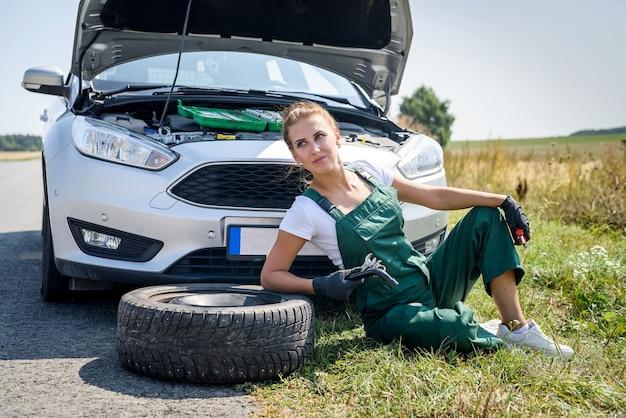 Piękna kobieta w kombinezonie z kluczykami naprawiająca zepsuty samochód w swojej podróży