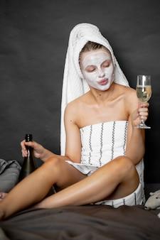 Piękna kobieta w kosmetycznej masce i ręczniku nalewa szampana do szklanki, siedząc na łóżku i uśmiechając się