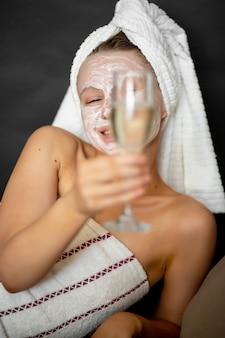 Piękna kobieta w kosmetycznej masce i ręczniku trzyma kieliszek do wina z szampanem, siedząc na łóżku i uśmiechając się