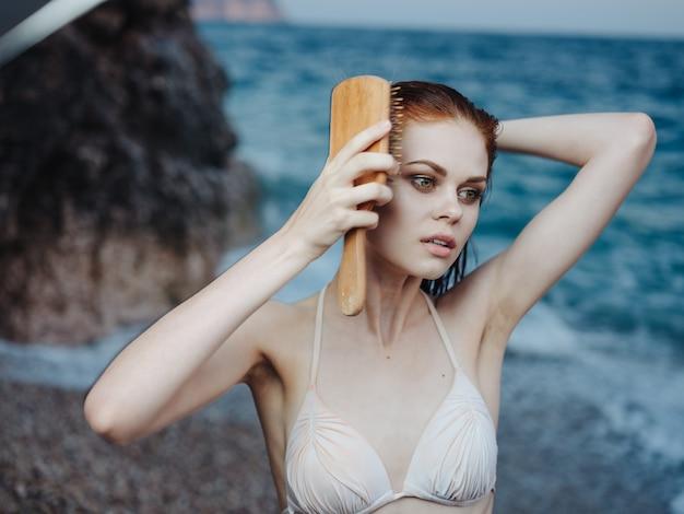 Piękna kobieta w kostiumie kąpielowym czesze włosy na głowie na łonie natury blisko morza.