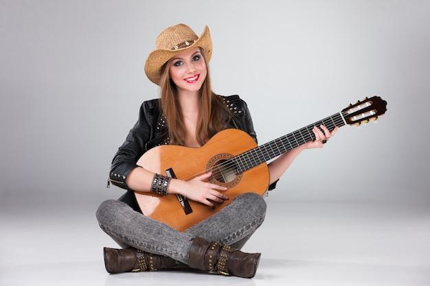Piękna kobieta w kowbojskim kapeluszu i gitarze akustycznej.