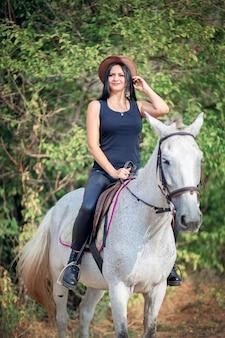 Piękna kobieta w kowbojskim kapeluszu i skórzanych spodniach jeździ na szarym koniu. szkolenie jeździeckie