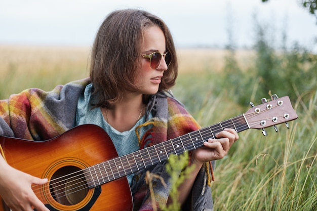 Piękna kobieta w krótkich fryzurach na sobie stylowe okulary przeciwsłoneczne odpoczynku na świeżym powietrzu, gra na gitarze, ciesząc się jej wakacji