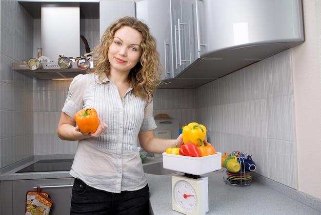 Piękna kobieta w kuchni z warzywami