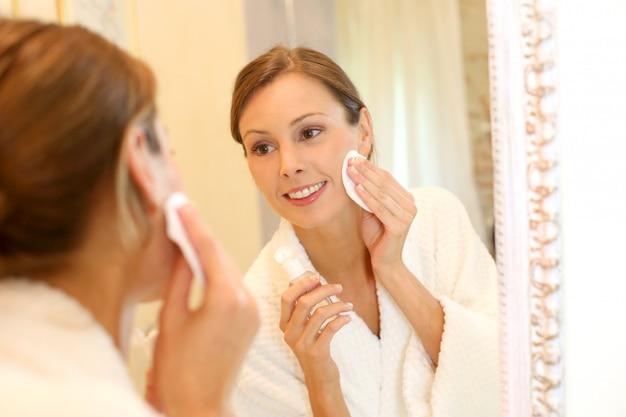 Piękna kobieta w łazience bierze makeup daleko