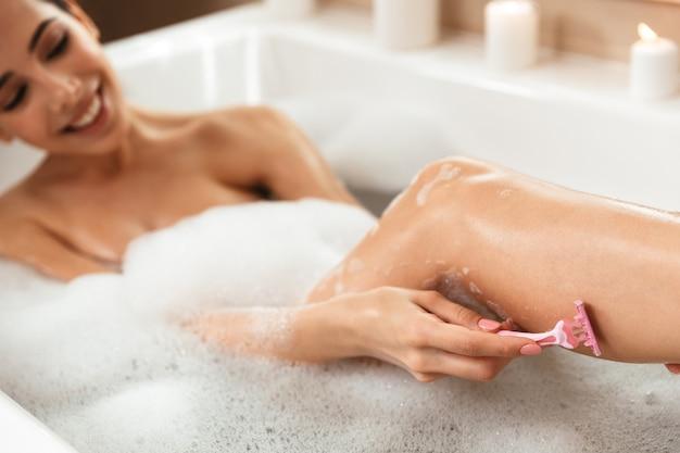 Piękna kobieta w łazience leży w wannie do golenia nóg.