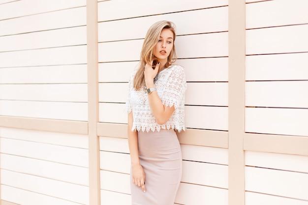 Piękna kobieta w letniej koszuli z koronką vintage stoi przy jasnej drewnianej ścianie