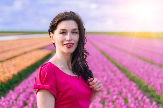 Piękna kobieta w letniej sukience stojącej na kolorowych polach kwiatów tulipanów