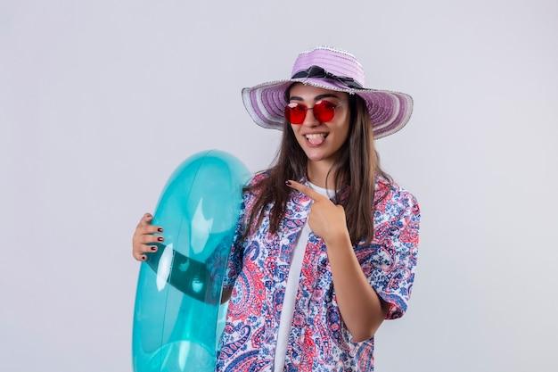 Piękna kobieta w letnim kapeluszu i czerwonych okularach przeciwsłonecznych trzymająca nadmuchiwany pierścionek wyglądający radośnie wystający język z radosną twarzą wskazującą palcem i ręką na bok stojącą nad białymi ba