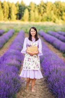 Piękna kobieta w liliowej sukience i fartuchu zbiera lawendę. zdjęcie lata. pielęgnacja kwiatów.