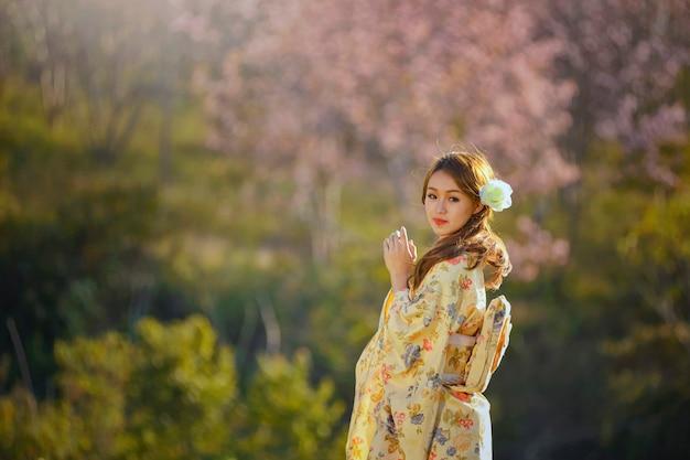 Piękna kobieta w magazynie w japonii, wiosenny kwiat wiśni sakura, różowe kwiaty sukura, styl vintage