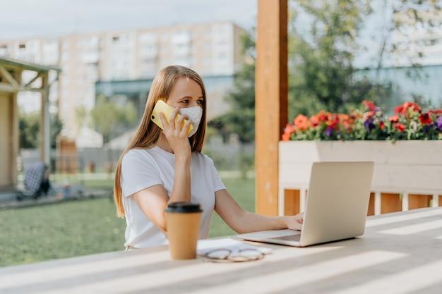 Piękna kobieta w masce medycznej rozmawia przez telefon i pracuje w laptopie usiąść