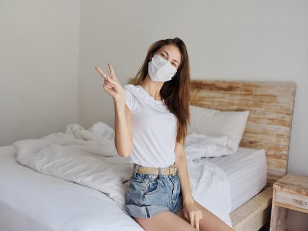 Piękna kobieta w masce medycznej siedzi na łóżku w jasnym pokoju i gestykuluje pozytywnie