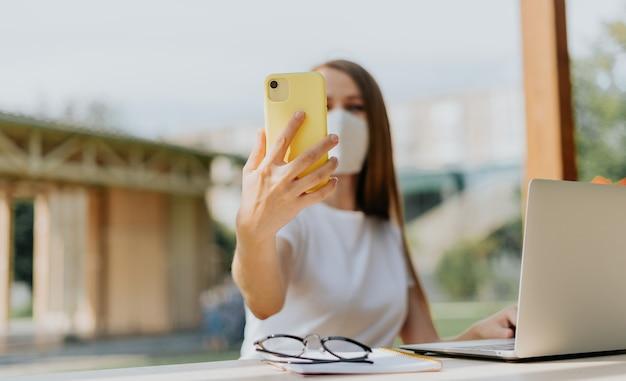 Piękna kobieta w medycznej masce ochronnej przy selfie