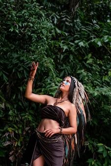 Piękna kobieta w nakryciu głowy piór ptaków. na jej policzku pomalowany niebieski kolor, dotyk dłoni zielonymi liśćmi, pozowanie modelki, koncepcja dżungli w lesie
