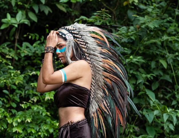 Piękna kobieta w nakryciu głowy z piór ptaków. na jej policzku pomalowano niebieski kolor