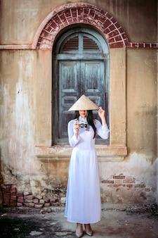 Piękna kobieta w narodowym stroju wietnamu stoi i łapie kapelusz przeciwsłoneczny. podczas robienia zdjęć