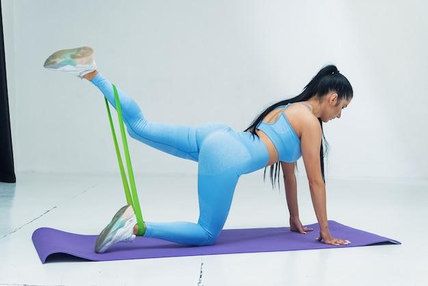 Piękna kobieta w niebieskiej odzieży sportowej robi ćwiczenia rozciągające za pomocą gumek fitness w kolorze białym