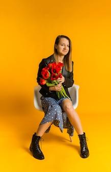Piękna kobieta w niebieskiej sukience i czarnej skórzanej kurtce siedzi na białym krześle i trzyma bukiet tulipanów na żółtej ścianie