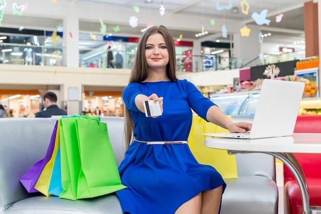 Piękna kobieta w niebieskiej sukience pokazująca kartę kredytową