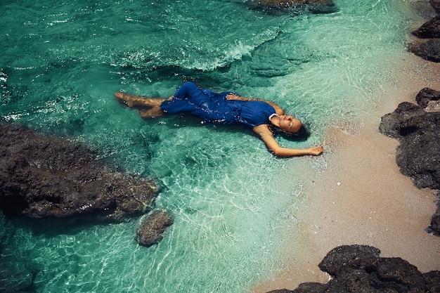 Piękna kobieta w niebieskiej sukience pozowanie na morzu