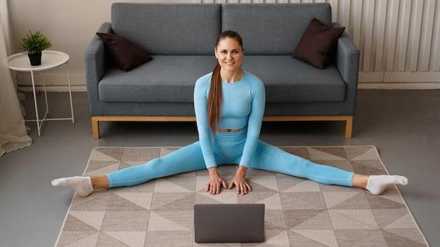 Piękna kobieta w niebieskim dresie rozciąga się w domu przed laptopem. siedzi na poprzecznym sznurku.