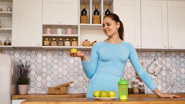 Piękna kobieta w niebieskim garniturze stoi w kuchni, uśmiecha się i trzyma zielone jabłko. pojęcie sportu i utraty wagi w domu.