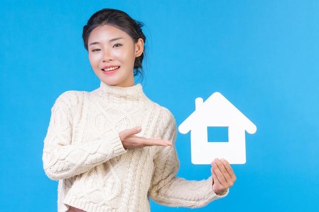 Piękna kobieta w nowej białej koszuli z długimi rękawami z symbolem domu. handel domami.