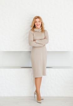 Piękna kobieta w obcisłej sukience, w butach na wysokim obcasie stoi z założonymi rękami, uśmiecha się i patrzy w kamerę.