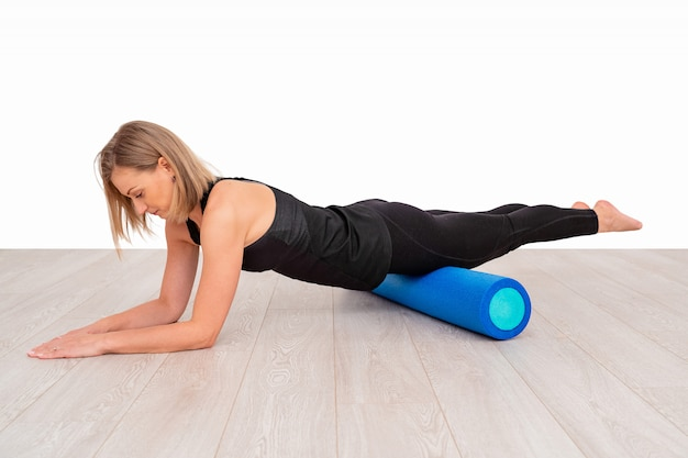Piękna kobieta w odzieży sportowej, instruktor pilates rozciągający i rozgrzewający wałkiem z pianki. ćwiczenie deski z naciskiem na sprawność rolki.