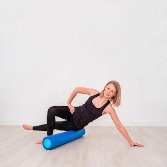 Piękna kobieta w odzieży sportowej, instruktor pilates rozciągający i rozgrzewający wałkiem z pianki